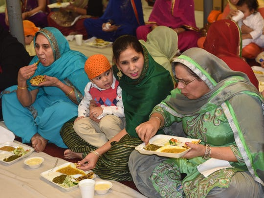 Visitors to the Sikh temple in Wappingers Falls share a meal together Sunday .