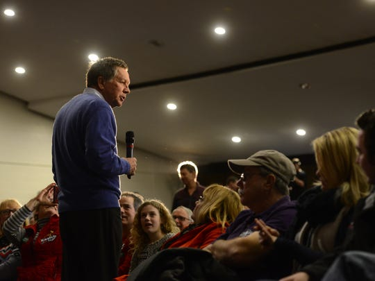 Republican presidential candidate and Ohio Gov. John Kasich holds a town hall rally at Colchester High School on Feb. 20, as Art Rovner of South Burlington, back, prepares to ask a question about climate change.