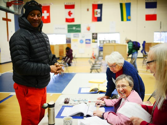 Burlington school board member Kyle Dodson jokes with poll workers Altana Bullard (rear) and Gloria Yandow (seated) at the Ward 1 polling station on March 1.