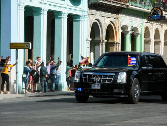 People watch along the street as the motorcade of President