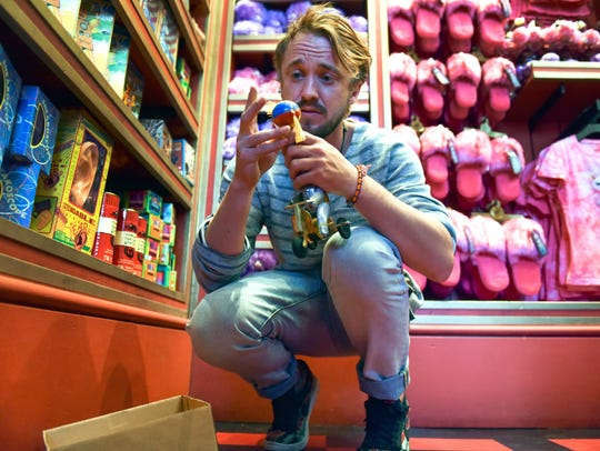 Tom Felton toys with the merchandise at Zonko's Joke