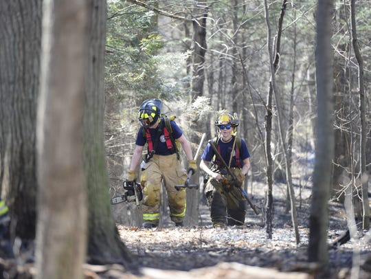 Firefighters cut down burning trees and rake leaves