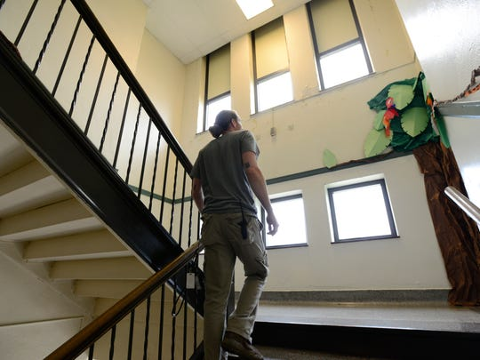 Chris Witmer, custodian at Stamm Elementary, shows the disrepair of the school around windows and walls.