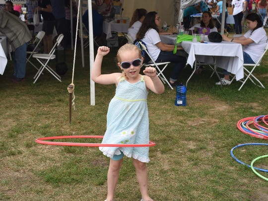 Scarlette Carpenter, 4, of New Paltz takes a turn on a hula hoop at Taste of New Paltz Sunday at the Ulster County Fairgrounds.