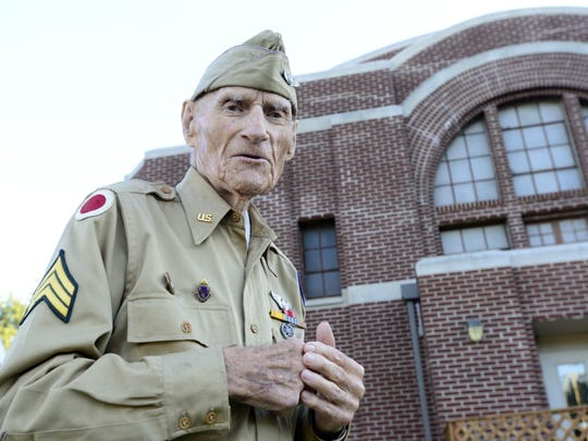 World War II veteran Jim McGrady, 98, of Fremont, stands in front of the Old Armory where he trained for his service. McGrady died Thursday.