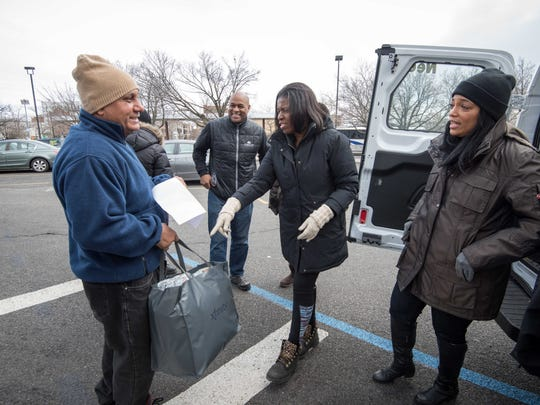 Asbury Park resident Andre Soto (left) gets a bag  from  Dorothy Debe and Yvette Anderson of Meet the Need.