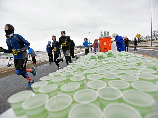 Cups of water are filled for runners as they pass by Sunday, Jan. 29, during the PoHo Hot Cocoa Run in Port Huron.