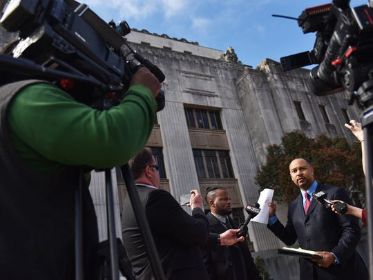 Attorney Carlos Moore, right, leads a press conference