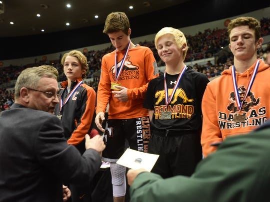 Silverton freshman Kaden Kuenzi accepts his state championship medal at the OSAA State Wrestling Championships at the Veterans Memorial Coliseum in Portland, Ore., on February 25, 2017. (Photo by: Alex Milan Tracy)