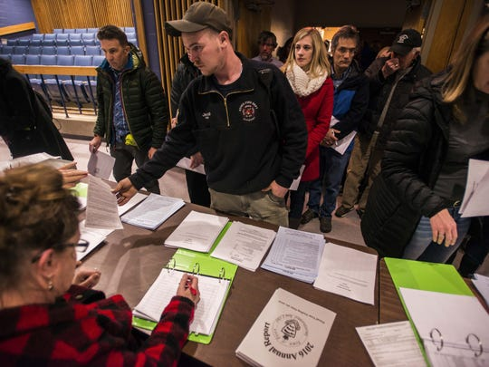 Essex firefighter Sean Jacob, center, checks in at the Essex town meeting Monday night, March 6, 2017, at the high school.