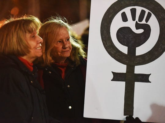 Patsy Booth and Margaret Terry hold a sign during International Women's Day rally held in Glen Rock.