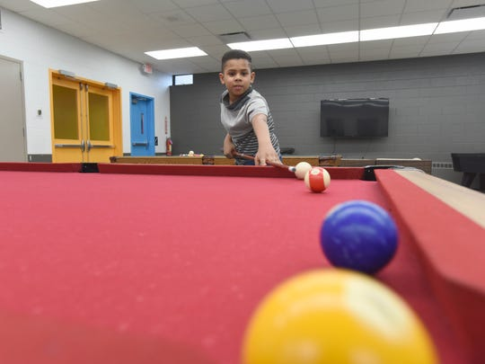 Eight-year-old Isaah Beato plays pool at the newly renovated Boys & Girls Club in Passaic.