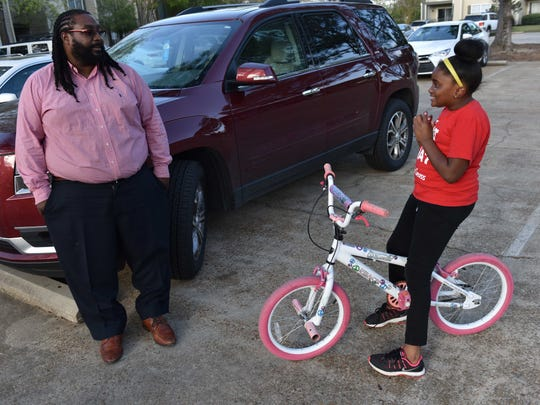 Kinyah Braddock and her father Demetrius Braddock negotiate rules about a timed bike riding game she plays.