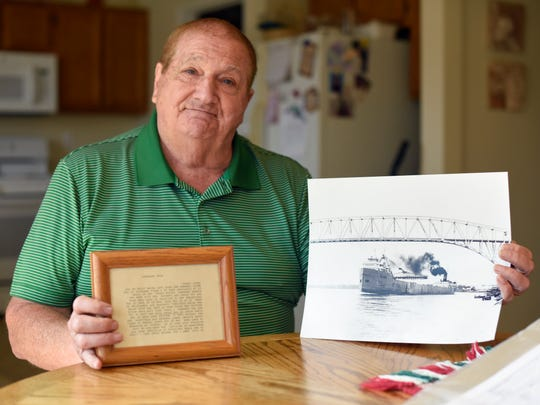 Russ Humphrey poses with a picture of the S.S. Carl D. Bradley and a quote from his story finding it Friday, April 14, at his home in Chesterfield Township.