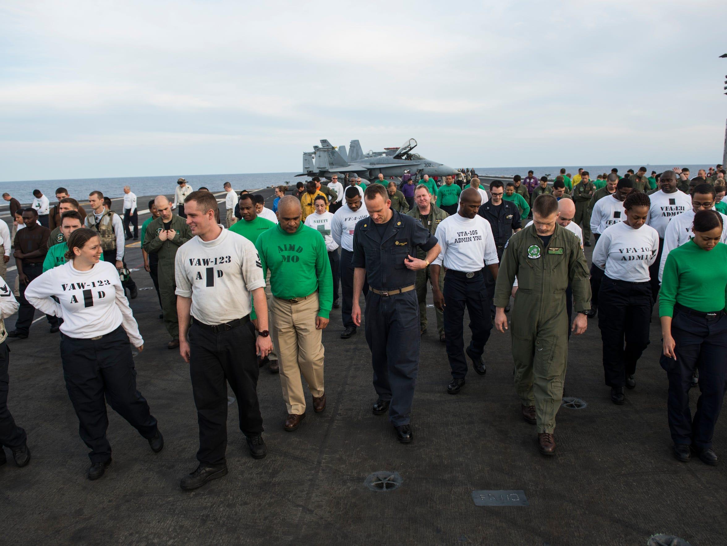 USS Eisenhower crew members walk the length of the