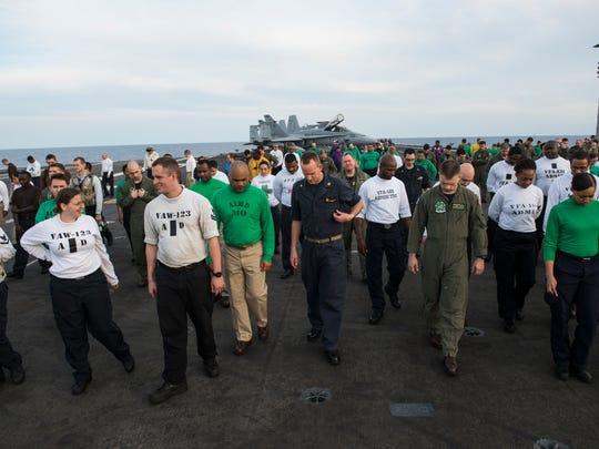 USS Eisenhower crew members walk the length of the flight deck.