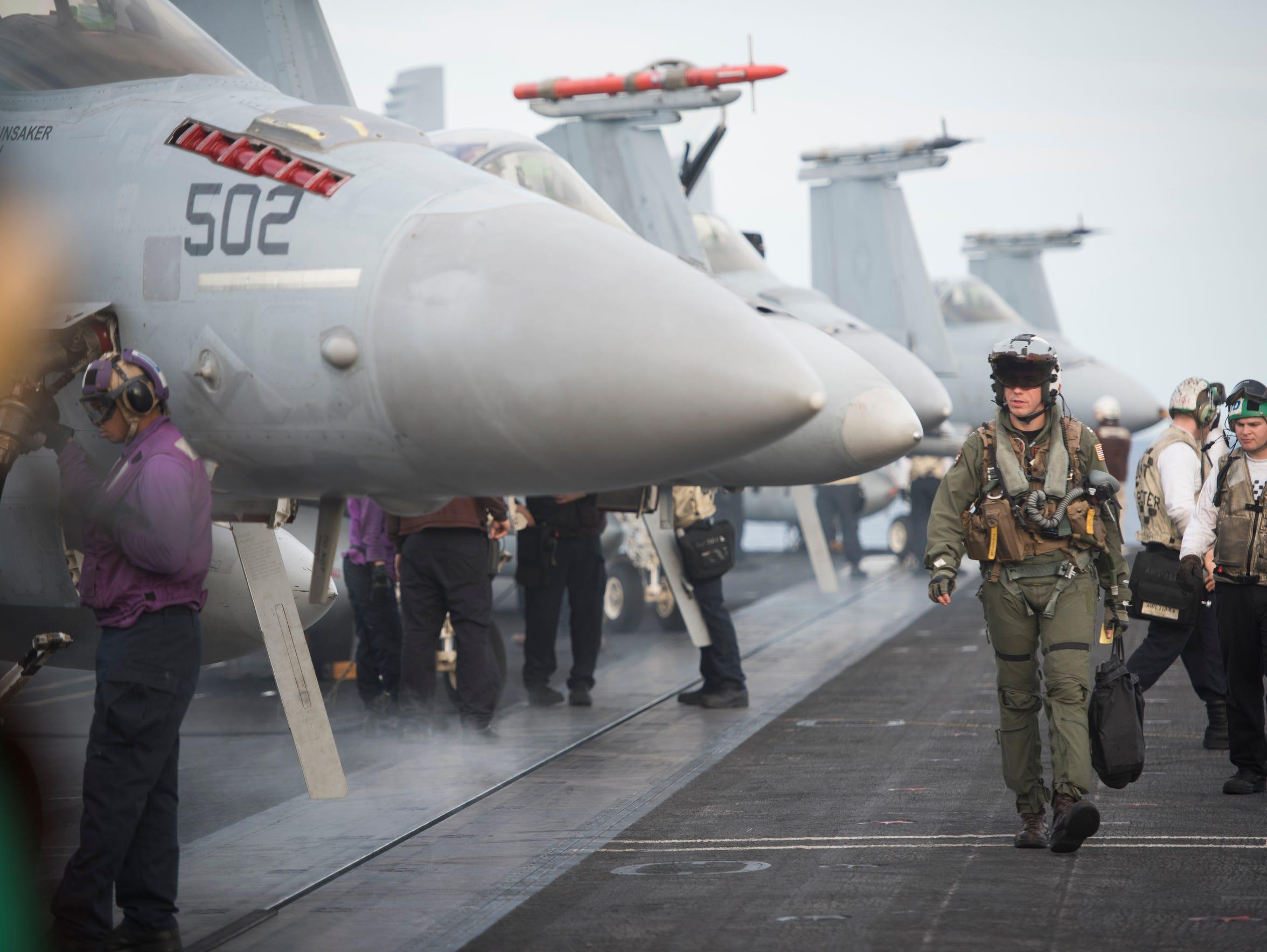 Hornet pilots walk on deck after landing on the USS