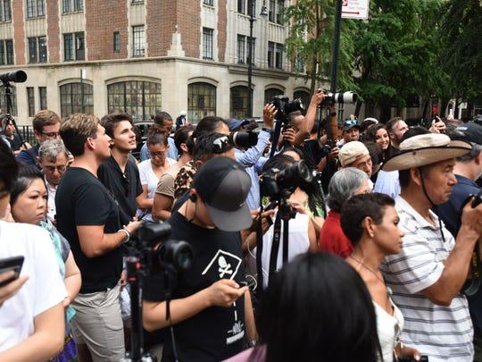 People crowd the street to photograph Manhattanhenge.
