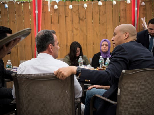 Senator Cory Booker talks with Nour Ajouz, a Syrian refugee, at Abu Rass restaurant in Paterson on Sunday, July 30, 2017.