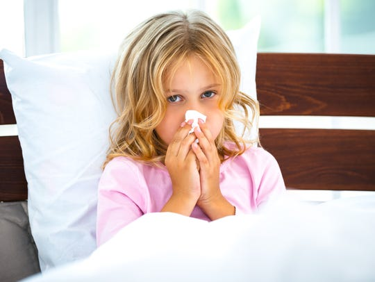 A little girl sits in bed with a runny nose.