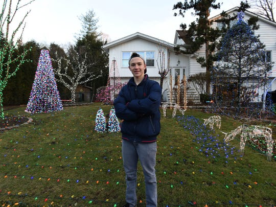 File Photo: In 2017, Daniel Eisenberg stands in front of his yard containing over 115,000 Christmas lights, synchronized to modern mashups of classic Christmas songs being broadcasted from a low-power radio station in his basement.