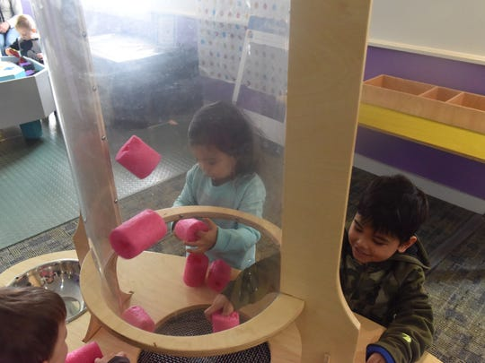 Simone Frascarelli, 2, and Filippe Frascarelli, 5, play with foam cylinders at one of the science stations on Sunday. They celebrated New Year's at noon along with other kids in the Mid-Hudson Children's Museum.