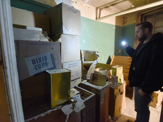 Gary Salvatoriello, supervisor of building and grounds at the Passaic Public Library, checks boxes of survival supplies inside the fallout shelter at the Reid Memorial Branch.