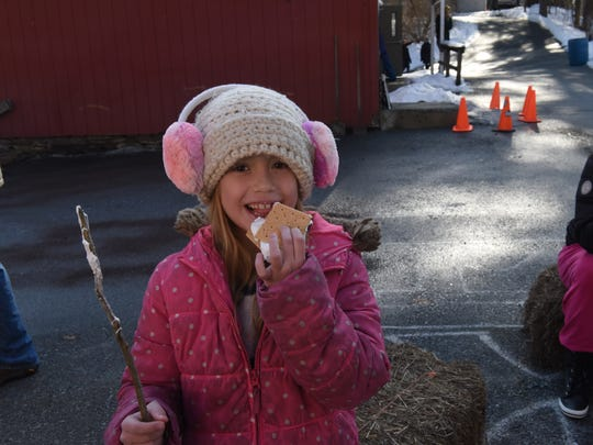 Lauren Dunning, 8, eats a s'more on Sunday. She and her younger sister didn't want to burn their marshmallows and kept them gooey.