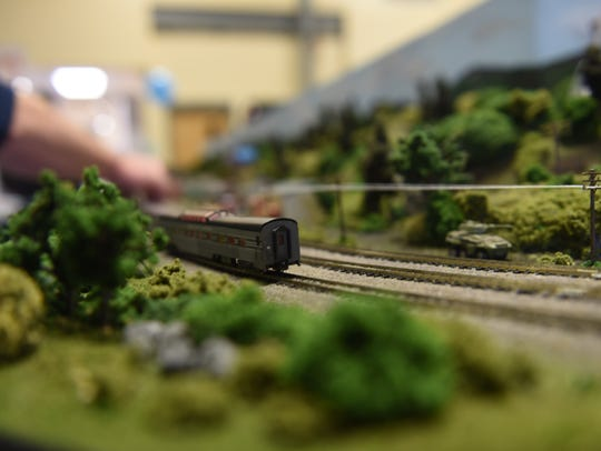 A toy train comes around a corner of a railroad on