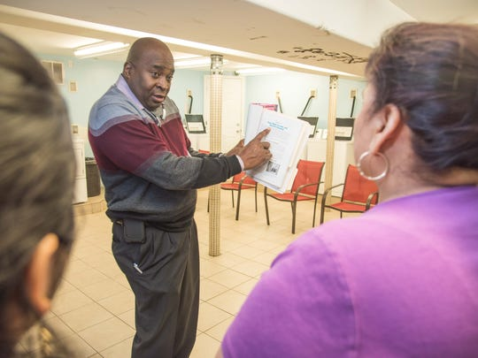 Mike McNeil, the fair housing officer for Lakewood, explains tenants rights to members of the Cottage Manor Apartments tenants association.