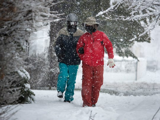 (right) Umut Topdemir walks arm in arm with his father Ibrahim Topdemir, who is blind and is visiting from Trilye in Turkey, as snow falls in Lyndhurst on Wednesday, March 7, 2018.