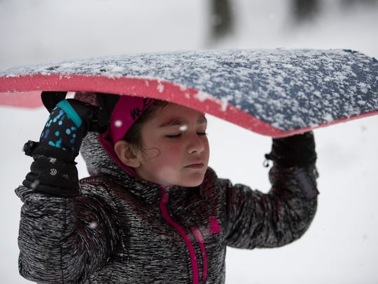 Jasmine Sims, 7, uses her sled to shield herself from