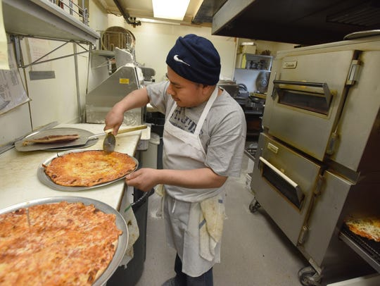 Carlos Cordero makes pizzas at Kinchley's Tavern in