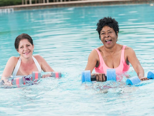 Two mature multi-ethnic women doing water aerobics