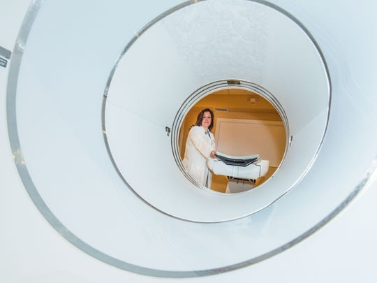 Dolores Ambrosy, imaging manager of Personal Care Molecular Imaging in Wall looks through a PET/CT scanner. Photo/James J.Connolly/Correspondent