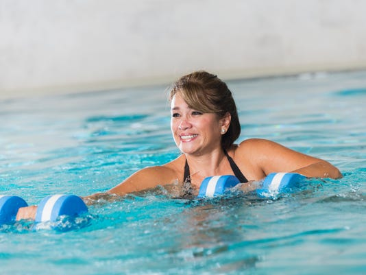 Middle aged Latin woman doing water aerobics exercise