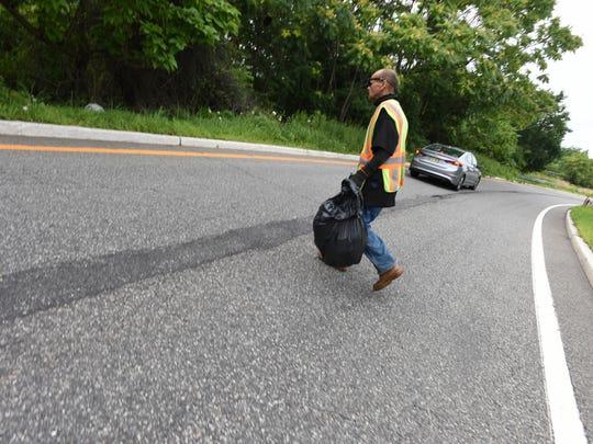 Paterson resident Benino Gonzalez picks up trash on Rt 19 in Paterson.