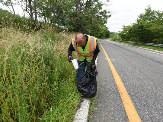 Paterson resident Benino Gonzalez picks up trash on