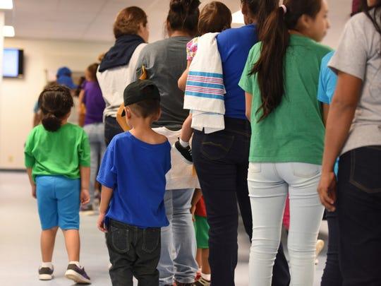 Madres inmigrantes y sus hijos hacen fila para recibir