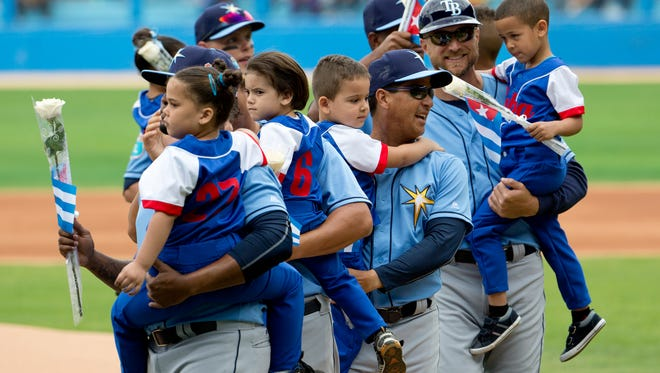 Members of the Tampa Bay Rays carry local Cuban children during opening ceremonies prior the start of an exhibition baseball game against the Cuban National team at the Estadio Latinoamericano, Tuesday, March 22, 2016, in Havana, Cuba. President Barack Obama and Cuban President Raul Castro also attended the exhibition game. (AP Photo/Pablo Martinez Monsivais)