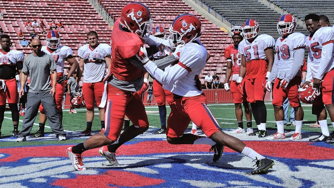 Fresno State players participate in the bull-in-the-ring drill.