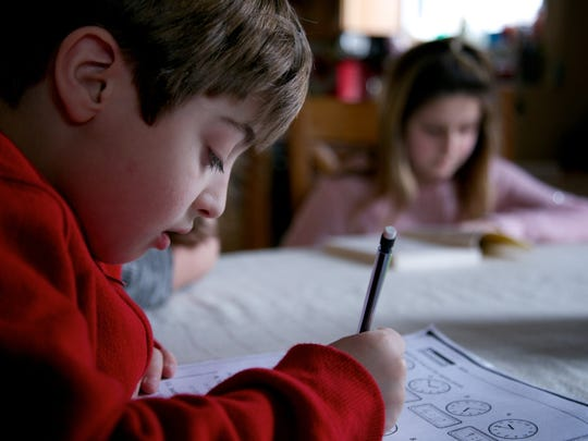 Asher Corbin, 8, and his sister Quinn Corbin, 10, work on homework Mark 4 in their home in Mt. Clemens.