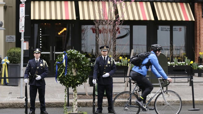 A Boston Police honor guard is posted outside the Forum restaurant, the site of the second of two bombs that exploded near the finish line of the 2013 Boston Marathon, Tuesday, April 15, 2014 in Boston. Three were killed and more than 260 injured in last year's explosions near the finish line of the race. (AP Photo/Charles Krupa)