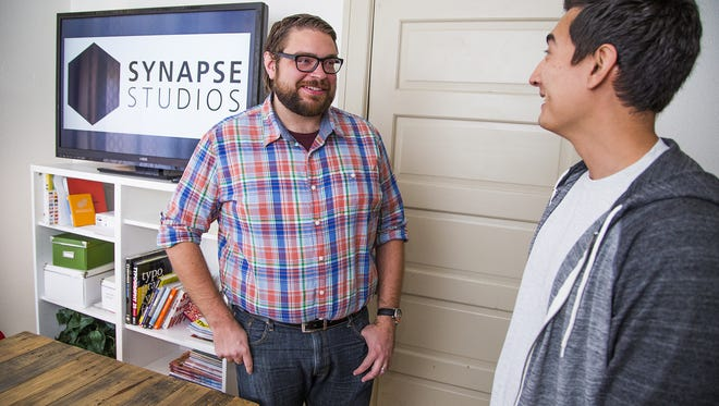 Chris Cardinal, co-founder and co-owner of Synapse Studios, left, talks with Pete Cavagnaro, quality assurance manager,  in the company offices on Mill Avenue in Tempe, Friday, November 6, 2015.
