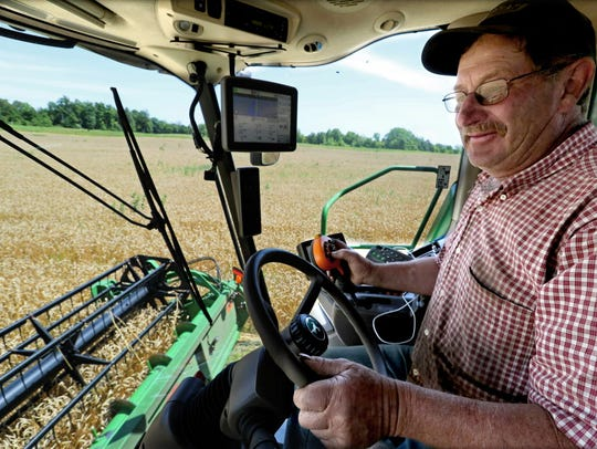 Bob Roden works combining a field of winter wheat on his farm near West Bend in July.