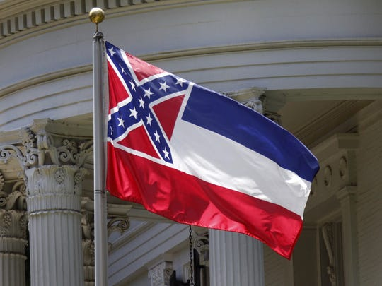 The Mississippi state flag is unfurled against the front of the Governor's Mansion in Jackson, Miss.