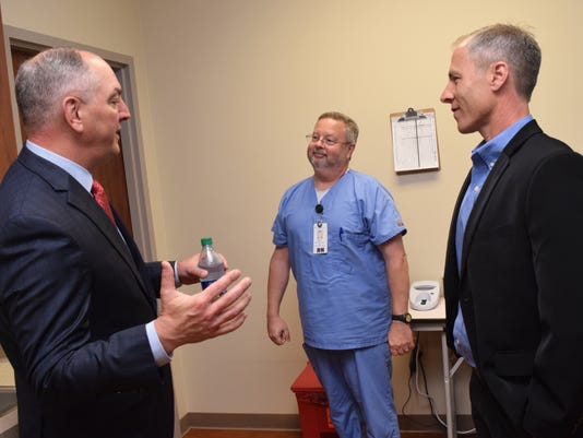 La. Gov. John Bel Edwards (left) talks with Billy Look (center), RN, a supervisor at the Christus Community Clinic on South MacArthur Drive in Alexandria, and Billy McRae (right), director of the Christus Community Health Clinics, about the care provided