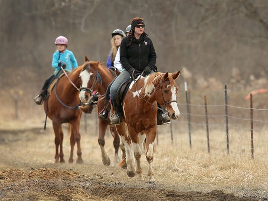 Bri Weibel leads a group of horse riders on a trail ride Saturday, January 31, 2015, at Natural Valley Ranch in Brownsburg.
