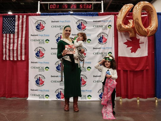 International half marathon participant Fadia Cudry of Dearborn Heights, poses for a photo with her daughter Noor Kadiri, 2, center, and Fatima Kadiri, 4, both of Dearborn Heights during the Metro Detroit Chevy Dealers Health & Fitness Expo at the Cobo Center in downtown Detroit, Friday, October 13, 2017.
