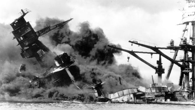 In this Dec. 7, 1941 file picture, the battleship USS Arizona belches smoke as it topples over into the sea during a Japanese surprise attack on Pearl Harbor. Two sets of brothers from Cincinnati died in the attack.